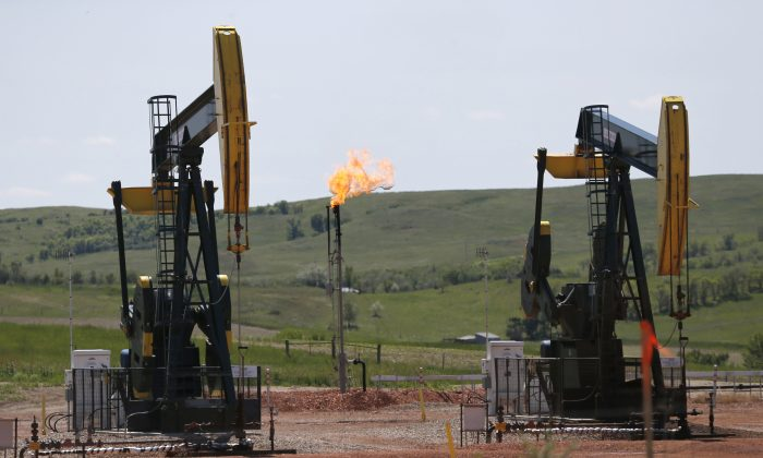 Oil is pumped and natural gas is flared off on an oilfield near Watford City, N.D. on June 12, 2014. (AP Photo/Charles Rex Arbogast)