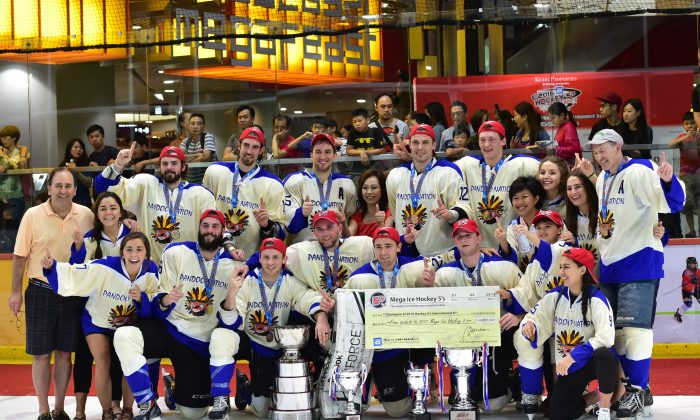 Nation celebrate their victory in the in the International division of the 2016 Mega Ice Hockey 5s, at Mega Ice on Saturday May 7, 2016, together with Ms Czarina Man, Director of MegaBox and a few of their special friends. (Bill Cox/Epoch Times)