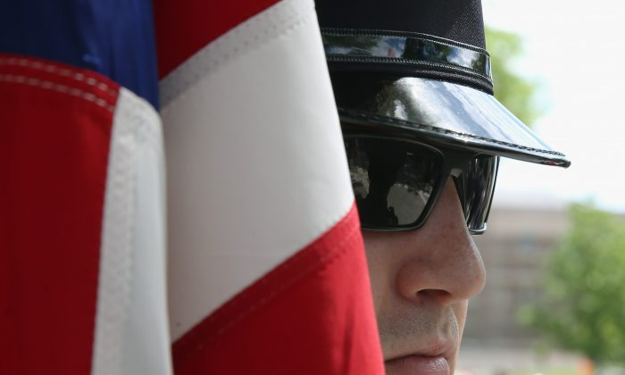 A member of the U.S. Immigration and Customs Enforcement Honor Guard holds an American flag during a ICE Valor Memorial wreath laying Ceremony at the National Law Enforcement Officers Memorial in Washington, D.C., on May 11, 2015. (Mark Wilson/Getty Images)