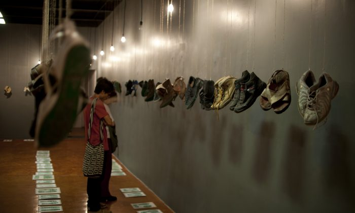 """People look at footprints as shoes of relatives of missing people with messages printed on their soles hang from the roof of the """"Casa de la Memoria Indomita"""" museum during the opening of the """"Huellas de La Memoria"""" (Memory Tracks) exhibition in Mexico City on May 9, 2016.  (YURI CORTEZ/AFP/Getty Images)"""
