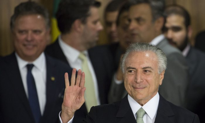 Brazil's acting President Michel Temer arrives to speak, at Planalto presidential palace in Brasilia, Brazil, Thursday, May 12, 2016, after the Senate voted to suspend President Dilma Rousseff pending an impeachment trial. In his first words to Brazilians as acting president, the former vice president said his priority will be reviving Latin America's largest economy. (AP Photo/Felipe Dana)