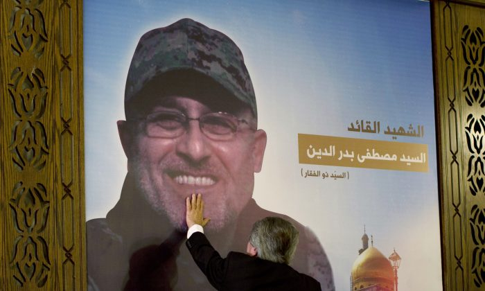 """Adnan Badreddine, brother of top Hezbollah commander Mustafa Badreddine, grieves at his brother's picture in a southern suburb of Beirut, Lebanon, Friday, May 13, 2016. Lebanon's militant Hezbollah group said Friday that its top military commander who was supervising its military operations in Syria, Mustafa Badreddine, was killed in an explosion in Damascus, a major blow to the Shiite group which has played a significant role in the conflict next door. Words in Arabic say """"The martyr commander Mustafa Badreddine"""". (AP Photo/Hassan Ammar)"""