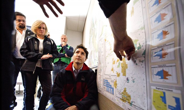 Canadian Prime Minister Justin Trudeau is given a briefing at the Regional Emergency Operation Centre during a visit to Fort McMurray, Alberta, Canada, on May 13, 2016. Alberta officials say 2,432 structures have been destroyed, 530 damaged, and 25,000 saved. The fire is now 930 square miles (2,410 square kilometers) in size and has moved away from the city. It's expected to burn in forested areas for at least a few more weeks. (Jason Franson/The Canadian Press via AP)