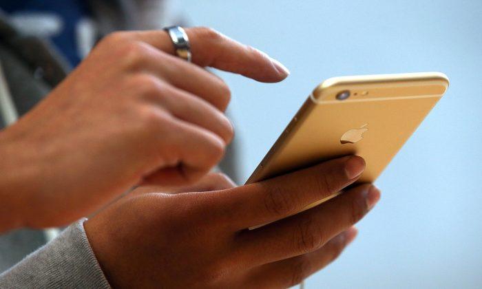 A consumer looks at an iPhone screen in Palo Alto, California. (Photo by Justin Sullivan/Getty Images)