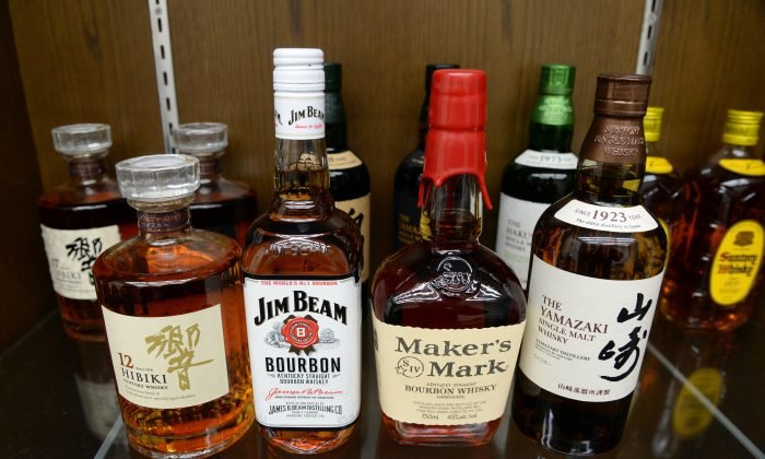 Japanese drink giant Suntory's whisky Yamazaki (R), Hibiki (L) and US beverage giant Beam's bourbon whisky Jim Beam (2nd L), Maker's Mark (2nd R) are displayed at Suntory's office in Tokyo on January 14, 2014. (YOSHIKAZU TSUNO/AFP/Getty Images)
