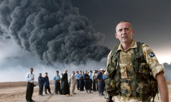 A British soldier secures an area near the burning oil export pipeline from the southern city of Basra, Iraq, March 24, 2004. (Joseph Barrak/AFP/Getty Images)