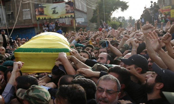 Hezbollah supporters carry the coffin of their slain commander Mustafa Badreddine, draped in a Hezbollah flag, during his funeral procession in a southern suburb of Beirut, Lebanon, on May 13, 2016. Badreddine died in an explosion in Damascus, a death that is a major blow to the Shiite group, which has played a significant role in the conflict next door. (AP Photo/Hassan Ammar)