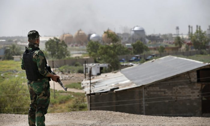 A federal police man stands guard outside the natural gas plant in Taji, 12 miles north of Baghdad, Iraq, on May 15, 2016. ISIS launched a coordinated assault Sunday on a natural gas plant north of the capital that killed more than a dozen people, according to Iraqi officials. (AP Photo)
