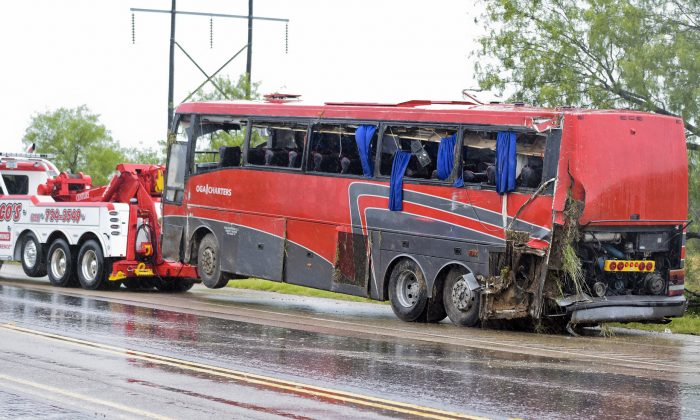 A damaged OGA Charters bus is hauled away after a fatal rollover on May 14, 2016, south of the Dimmit-Webb County line on U.S. 83 North in Texas. (Danny Zaragoza/Laredo Morning Times via AP)