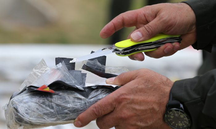 File: National Police Chief Gen. Rodolfo Palomino opens a package of seized cocaine to show to the press at a police station in Necocli, Colombia, Tuesday, Feb. 24, 2015. Palomino said police seized just over three tons of cocaine on Monday from the Los Usuga criminal gang in a rural area of Unguia in Choco state. (AP Photo/Fernando Vergara)