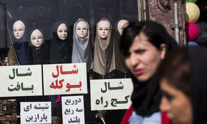 Iranian women walk past a shop displaying scarves on mannequins in downtown Tehran on February 24, 2016. (BEHROUZ MEHRI/AFP/Getty Images)