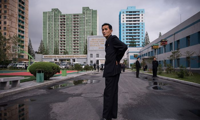 A guide stands in a courtyard outside the March 26 Electric Cable Factory in Pyongyang on May 6, 2016. (Ed Jones/AFP/Getty Images)