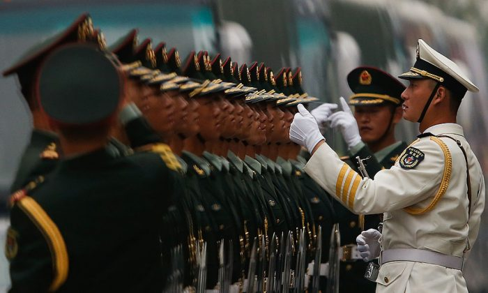 Chinese soldiers stand for inspection during a welcoming ceremony for Venezuela President Nicolas Maduro Moros in Beijing on Sept. 22, 2013. The Chinese regime has started dismantling business ventures run by its military. (Lintao Zhang/Getty Images)
