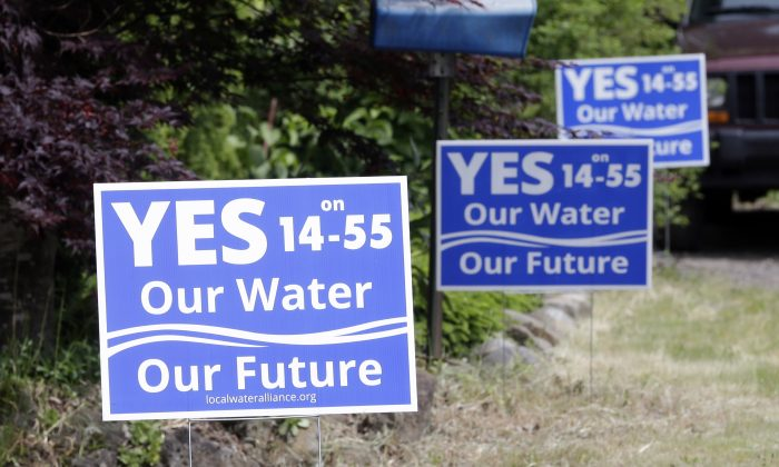 FILE - In this May 5, 2016 file photo, ballot measure yard signs regarding the issue of moving a Nestle spring water bottling plant into the small community, are shown in Cascade Locks, Ore. Oregon's scenic Columbia River Gorge is the stage for one of the hottest disputes in Oregon's Tuesday, May 17, 2016 primary — a proposal by Nestle to build a bottled water plant in Cascade Locks, using water from a mountain spring. (AP Photo/Don Ryan, file)
