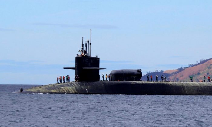 U.S. Navy crew stand on the USS Michigan (SSGN-727), an Ohio-class guided missile submarine, as it prepares to dock at Subic Freeport, a former US naval base Tuesday, March 25, 2014 about 70 kilometers (44 miles) west of Manila, Philippines. (AP Photo/Jun Dumaguing)