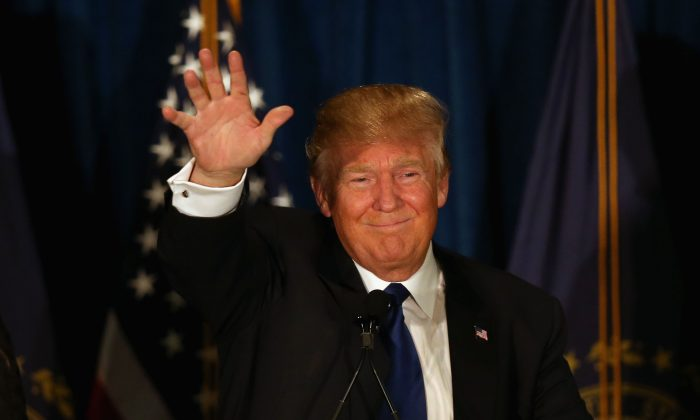 Republican presidential candidate Donald Trump waves to his supporters after Primary day at his election night watch party at the Executive Court Banquet facility on February 9, 2016 in Manchester, New Hampshire.  (Photo by Joe Raedle/Getty Images)