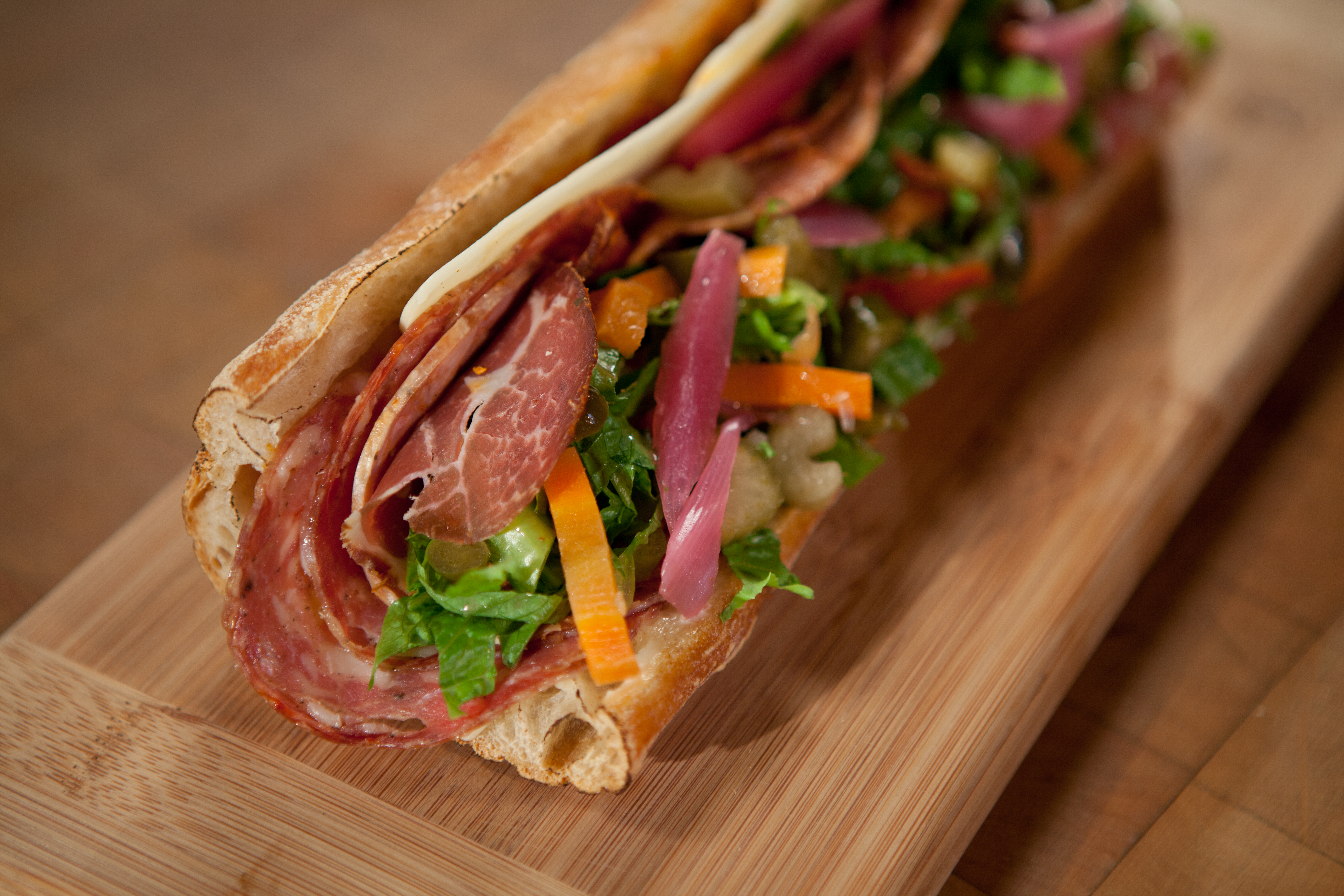 Make a stop at Goose the Market to stock up on local artisanal products and fantastic sandwiches like the Batali (above), a moreish combination of spicy salami meats, bright pickled onions, and provolone. (Courtesy of Goose the Market)