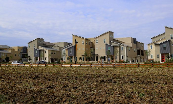 This photo taken April 8, 2016, shows town homes at The Cannery, which is set beside the plowed field of the small, urban farm that is a centerpiece of the community in Davis, Calif.  (Michelle Locke via AP)