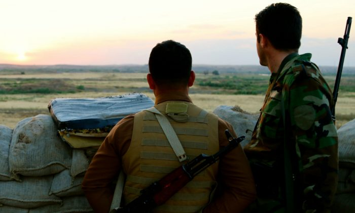 Kurdish soldiers look toward ISIS lines. (Nolan Peterson/The Daily Signal)