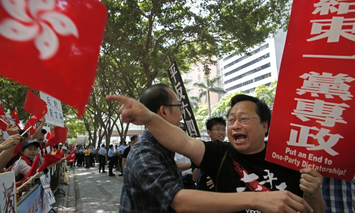 A pro-democracy activist, right, waves banner and shout slogans against pro-government protesters, left, outside the convention center where the Chinese Communist Party's third-highest ranking official, Zhang Dejiang, gave a speech during a visit to Hong Kong, Wednesday, May 18, 2016.  Hong Kong authorities rolled out a massive security operation on Tuesday as they braced for protests during a top Beijing official's visit to the semiautonomous city, where tensions are rising over Chinese rule.(AP Photo/Vincent Yu)