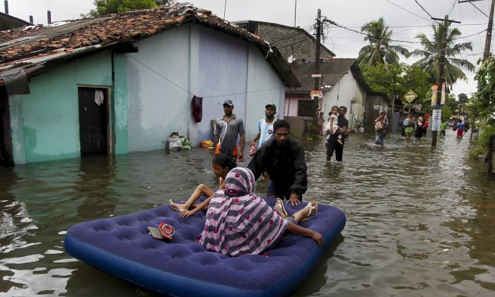An elderly Sri Lankan woman and a girl are shifted on a mattress at a flooded area in Colombo, Sri Lanka, Tuesday, May 17, 2016. The Disaster Management Center said that 114 homes have been destroyed and more than 137,000 people have been evacuated to safe locations as heavy rains continue. (AP Photo/Eranga Jayawardena)