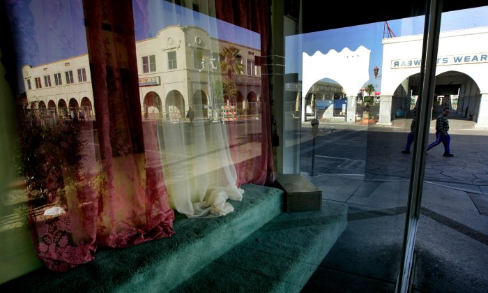 FILE - This April 15, 2010 file photo, a storefront window sits empty as downtown Calexico, Calif. is reflected in the glass. The U.S. Justice Department issued a scathing review Wednesday, May 18, 2016, of the small town's police practices in a big drug and immigrant smuggling corridor on California's border with Mexico, finding a lack of basic controls and oversight of criminal investigations, unstable leadership and other red flags. (AP Photo/Sandy Huffaker,File)
