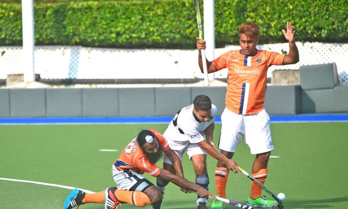 Khalsa-A's Ari Ali (far right) and Harsmarjit Singh keep SSSC-A's Kulvinder Singh at bay in their Holland Cup final at King's Park on Sunday May 15, 2016. (Eddie So)