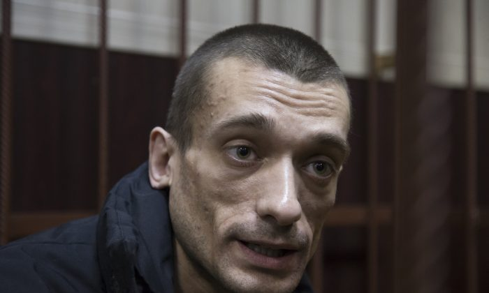 Russian artist Petr Pavlensky speaks to journalists as he sits in a cage in court room in Moscow on March 31, 2016. (AP Photo/Ivan Sekretarev, file )