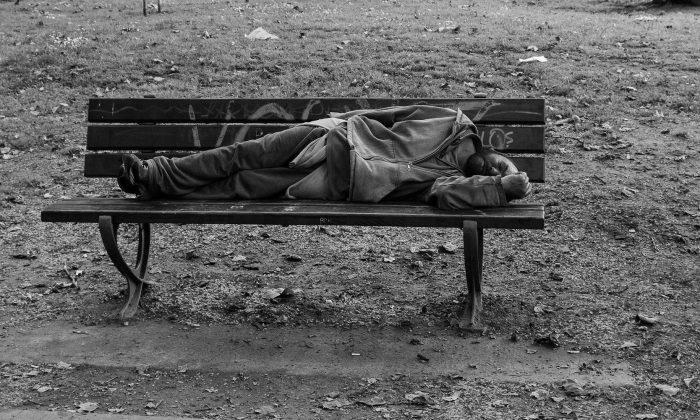 A homeless man sleeps on a park bench. (Public domain)