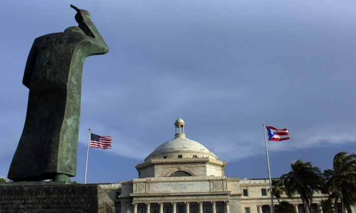 A bronze statue of San Juan Bautista stands in front of Puerto Rico's Capitol as U.S. and Puerto Rican flags fly in San Juan, Puerto Rico, on July 29, 2015. (AP Photo/Ricardo Arduengo)