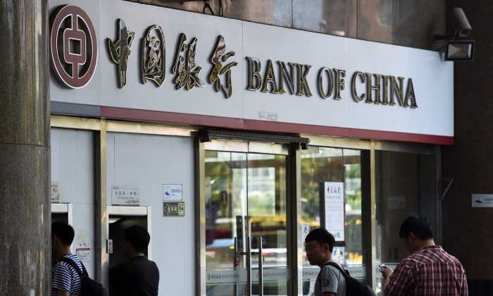People wait outside a Bank of China branch in Beijing. On May 26, the bank is issuing China's first NPL securitization deal since 2008. (Greg Baker/AFP/Getty Images)