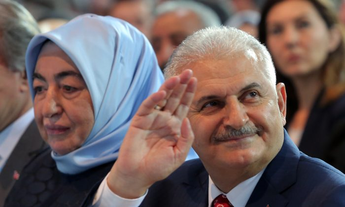 Binali Yildirim, Turkey's current Transportation Minister and founding member of the AKP, Turkey's governing party, and his wife Semiha Yildirim salute supporters during party congress in Ankara, Turkey, on May 22, 2016. Turkey's ruling party held a special convention on Sunday to confirm Binali Yildirim, a longtime ally of President Recep Tayyip Erdogan as its new chairman and next prime minister, a move that is likely to consolidate the Turkish leader's hold on power. (AP Photo/Riza Ozel)