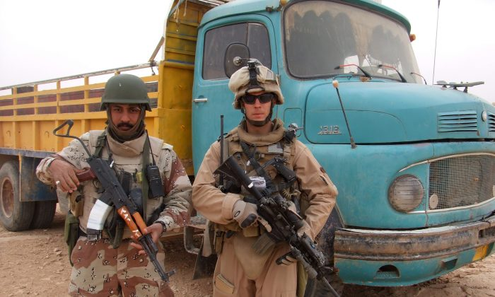 Chase Millsap with the Captain standing next to a suspected truck bomb following a successful raid in Al Anbar, Iraq. (Chase Millsap via AP)