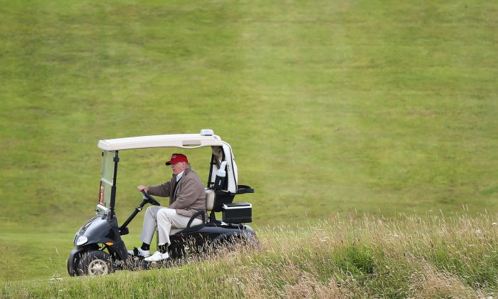 In this July 31, 2015 file photo, Republican presidential candidate Donald Trump drives his golf buggy during the second day of the Women's British Open golf championship on the Turnberry golf course in Turnberry, Scotland. (AP Photo/Scott Heppell)