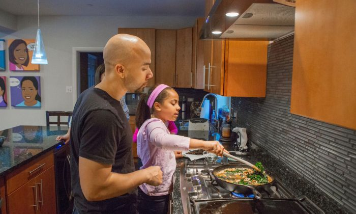 Taryn Robinson cooks white turkey chili, a meal kit dish from Blue Apron, as her father, Keith Robinson, watches over her shoulder in Evanston, Ill., on  Jan. 23, 2016. The industry of meal kits is growing quickly and competition is heating up as more players enter the space. (AP Photo/Teresa Crawford)