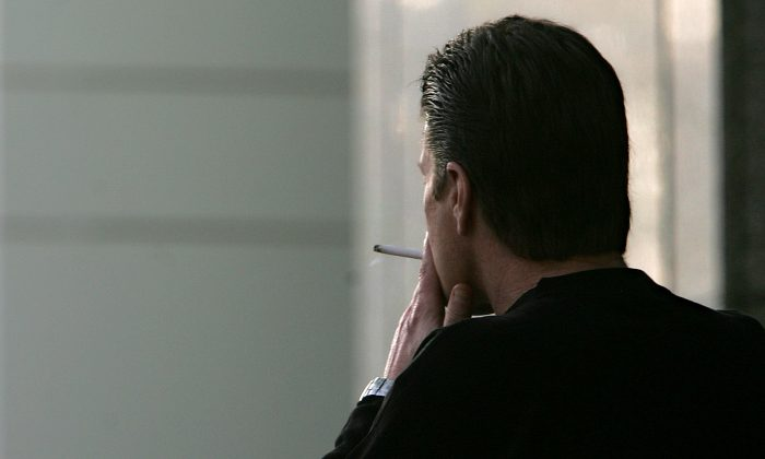 FILE - In this Dec. 13, 2005, file photo, an unidentified man smokes a cigarette in Sacramento, Calif. The adult smoking rate fell in 2015, with its largest annual decline in at least 20 years, according to a new government report. (AP Photo/Rich Pedroncelli, File)