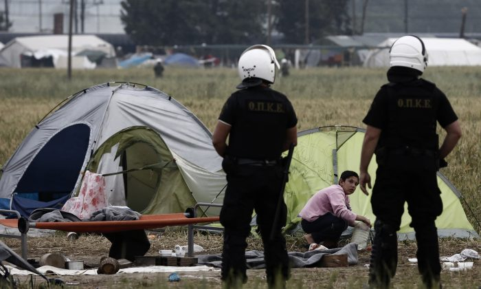Policemen stand next to tents during a police operation at a makeshift refugee camp at the Greek-Macedonian border near the northern Greek village of Idomeni, Tuesday, May 24, 2016. Greek authorities began an operation at dawn Tuesday to gradually evacuate the country's largest informal refugee camp of Idomeni on the Macedonian border, blocking access to the area and sending in more than 400 riot police. (Yannis Kolesidis/ANA-MPA via AP)