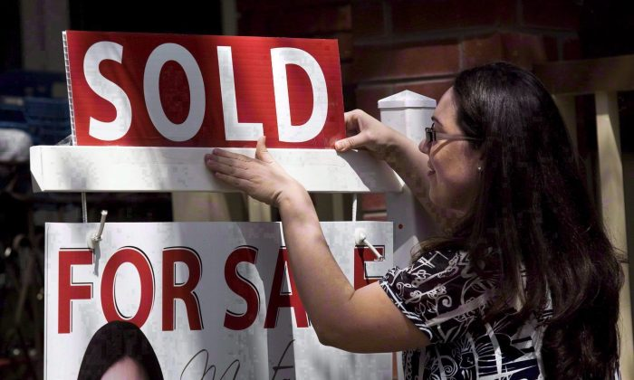 """A real estate agent puts up a """"sold"""" sign in front of a house in Toronto. Ottawa needs to beef up its efforts to combat money laundering in the real estate industry, critics say. (The Canadian Press/Darren Calabrese)"""