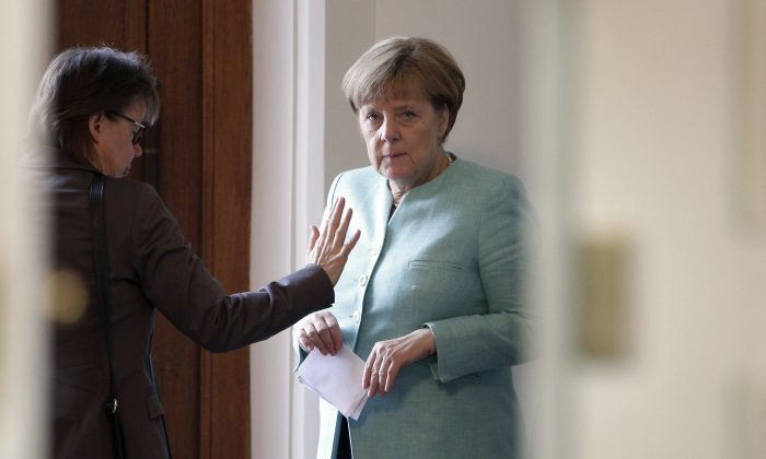 German Chancellor Angela Merkel (R) talks to her office manager Beate Baumann (L) prior to a cabinet meeting as part of a two-day retreat of the German government in Meseberg north of Berlin, Germany on May 25, 2016. (AP Photo/Michael Sohn)