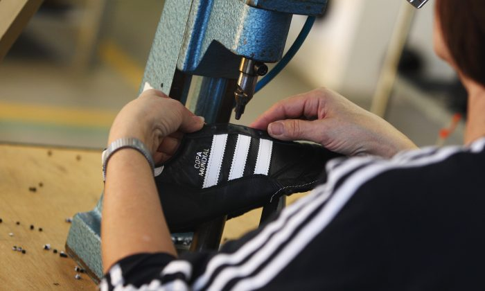 An employee pierces the shoelace holes for a handmade football boot at the factory of German sporting-goods maker Adidas AG on February 23, 2011 in Scheinfeld, Germany.  (Alex Grimm/Getty Images)