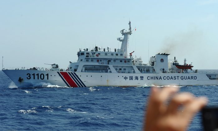 A Vietnamese coast guard officer photographs a Chinese coast guard vessel in disputed waters in the South China Sea on May 14, 2014. (Hoang Dinh Nam/AFP/Getty Images)