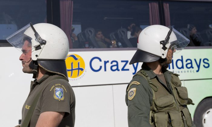 Greek police secure the passage of a bus carrying migrants evacuated from the makeshift camp in Idomeni, Greece, Tuesday, May 24, 2016. Greek authorities sent hundreds of police into the country's largest informal refugee camp Tuesday to support the gradual of evacuation of the Idomeni site on the Macedonian border. (AP Photo/Darko Bandic)