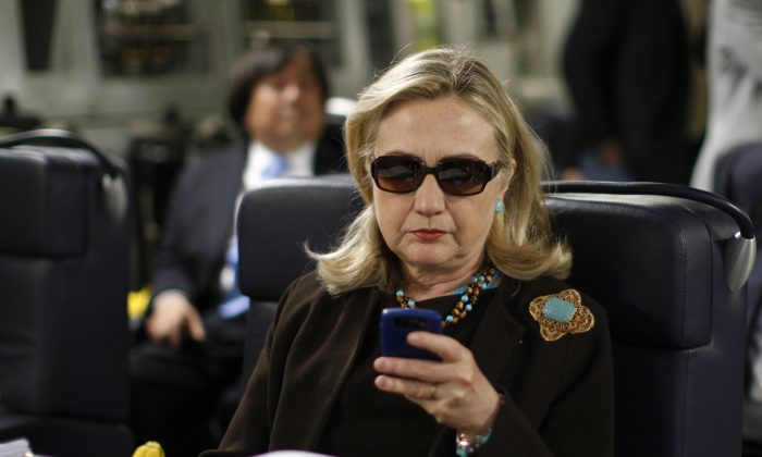 Hillary Rodham Clinton checks her Blackberry from a desk inside a C-17 military plane upon her departure from Malta, in the Mediterranean Sea, bound for Tripoli, Libya. (AP Photo/Kevin Lamarque, Pool)