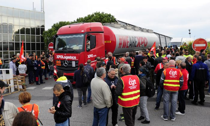"""Union activists block the entrance of the industrial area in Vitrolles near Marseille,  southern France, on a day of nationwide strikes and protests over a labor reform, Thursday, May 26, 2016. French Prime Minister Manuel Valls says he is open to """"improvements and modifications"""" in a labor bill that has sparked intensifying strikes and protests, but will not abandon it. (AP Photo/Franck Pennant)"""
