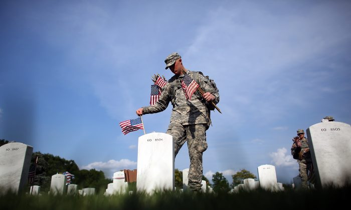 A member of the 3rd U.S. Infantry Regiment places American flags at the graves of U.S. soldiers buried in Section 60 at Arlington National Cemetery in preparation for Memorial Day in Arlington, Va., on May 24, 2012. (Win McNamee/Getty Images)
