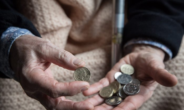 An elderly person looks at cash at home, near Bristol, England, on Feb. 16, 2015. (Matt Cardy/Getty Images)