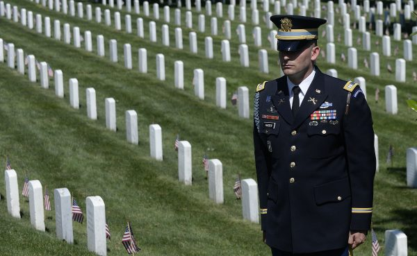 A member of the honor guard stands as the motorcade carrying U.S. President Barack Obama arrives for a Memorial Day ceremony at Arlington National Cemetery in Arlington, Va., on May 25, 2015. (Olivier Douliery/Getty Images)