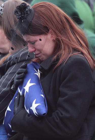 Kait Wyattt, widow of U.S. Marine Derek Wyatt, clutches the American flag which was draped over her husband's casket during funeral services at Arlington National Cemetery. (Courtesy of Arlington National Cemetery)