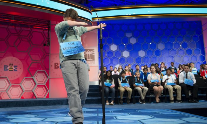 Mitchell Robson, 14, of Danvers, Mass., steps backwards while celebrating correctly spelling his word during the preliminary round three of the Scripps National Spelling Bee in National Harbor, Md., Wednesday, May 25, 2016. (AP Photo/Cliff Owen)