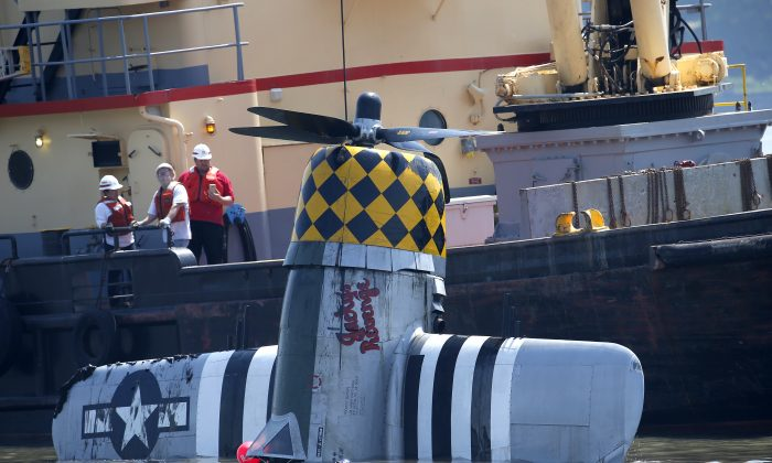 Officials remove a plane out of the Hudson River a day after it crashed, Saturday, May 28, 2016, in North Bergen, N.J. The World War II vintage P-47 Thunderbolt aircraft crashed into the river Friday, May 27,  killing its pilot. (AP Photo/Julio Cortez)